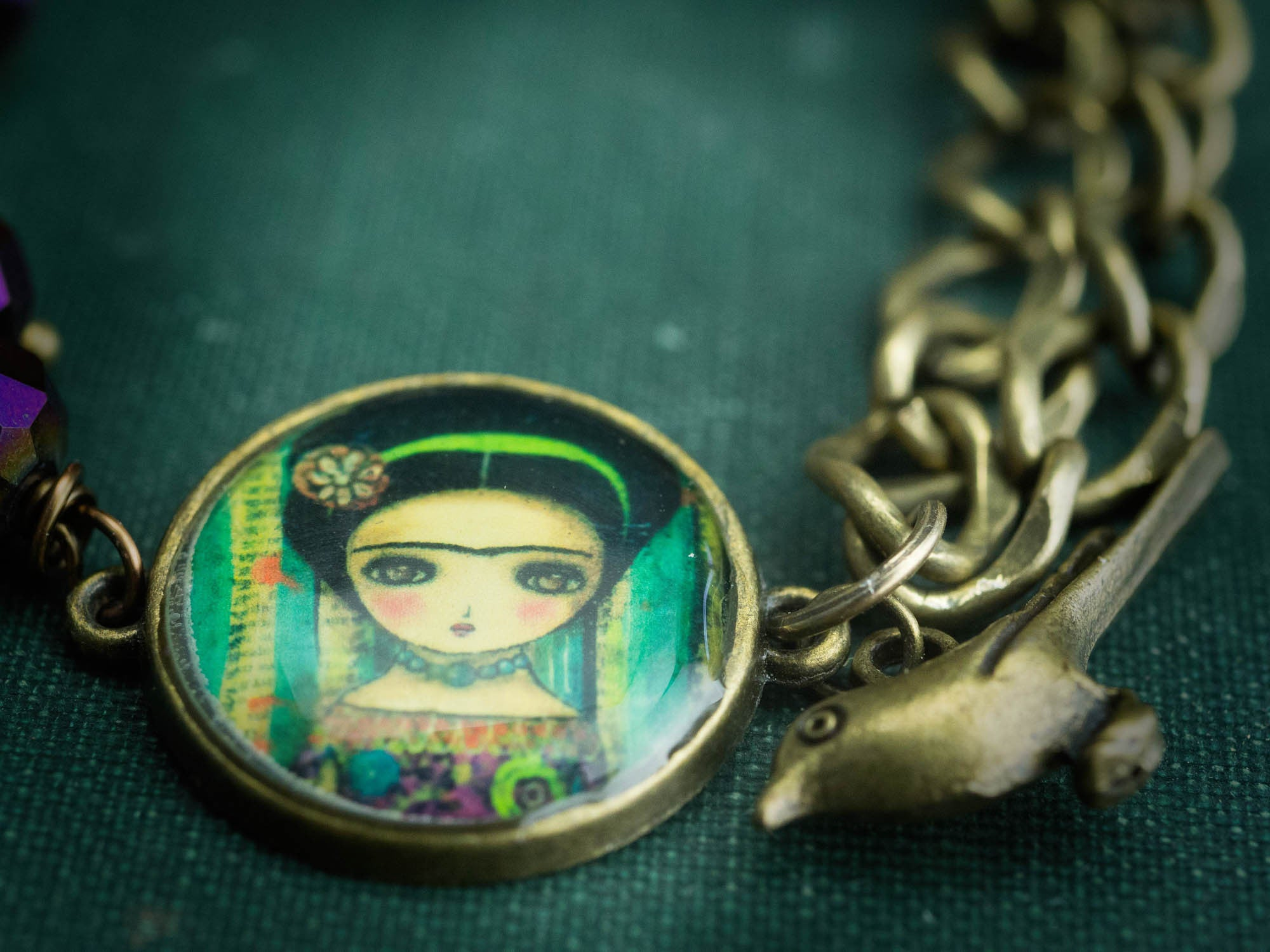closeup of original jewelry created by Danita Art. A metal chain, Frida Kahlo Round Cameo and purple glass beads.