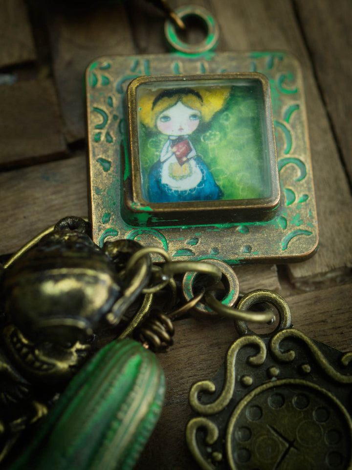 Alice in Wonderland, a mixed media painting by Danita converted into a metal charm on her original handmade wearable art jewelry.