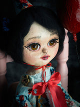 A girl dressed by hand in red and blue by dollmaker and online teacher Danita