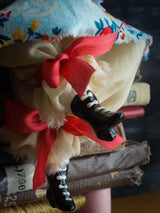 Boots on this art doll by danita are poured ceramic, hand painted and decorated by the dollmaking artist in her studio.