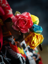 Frida art doll by Danita is holding a bunch of colorful paper roses in her hands.