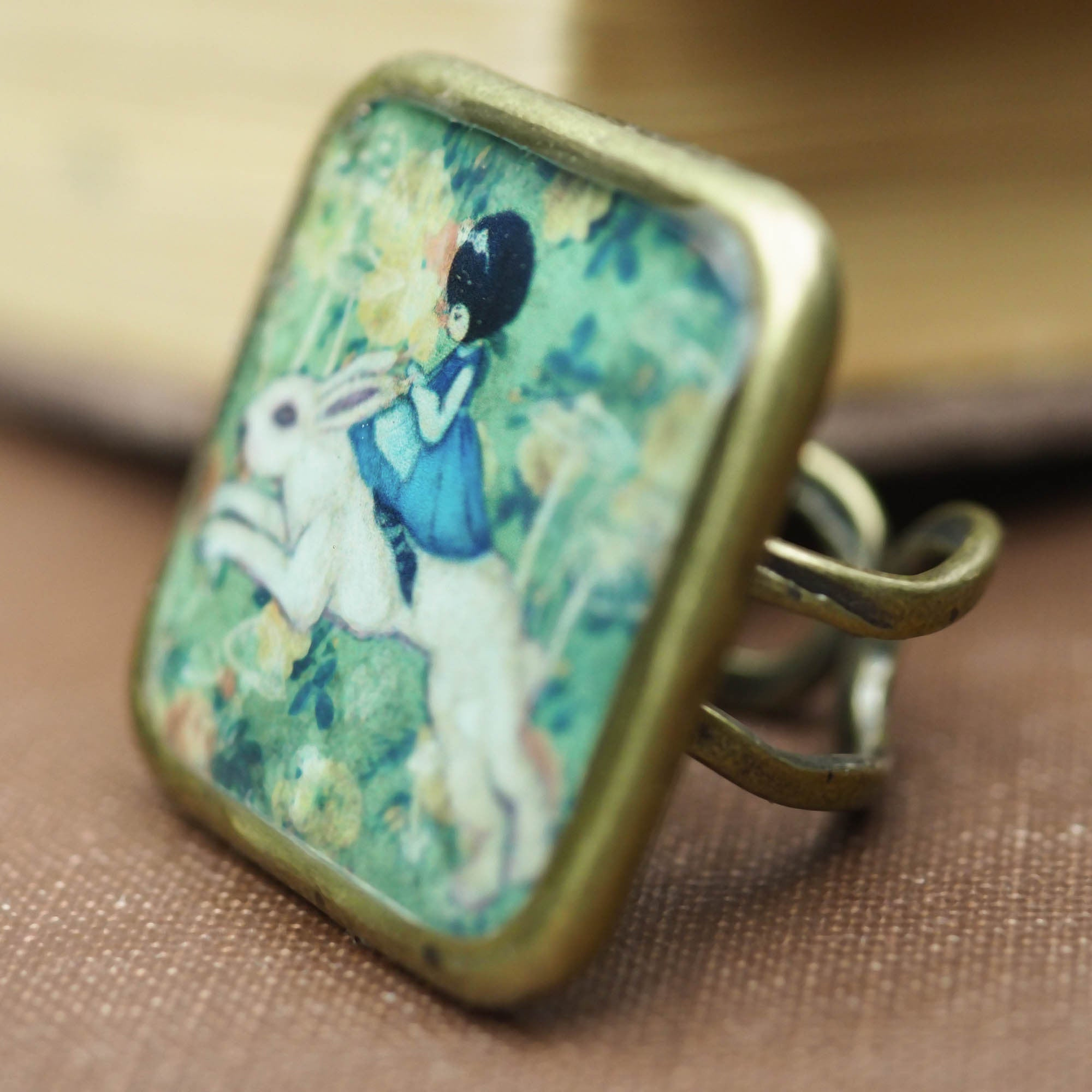 Alice riding the white rabbit in Wonderland square ring, Jewelry by Danita Art