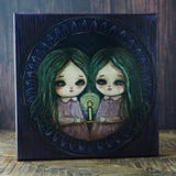 Sisters by candle light: An original mixed media painting by Danita. Mystery and horror mix in a whimsical image of two sisters exploring a haunted mansion by candlelight. Made with acrylics, oils, pencils, graphite and more over a stretched canvas.