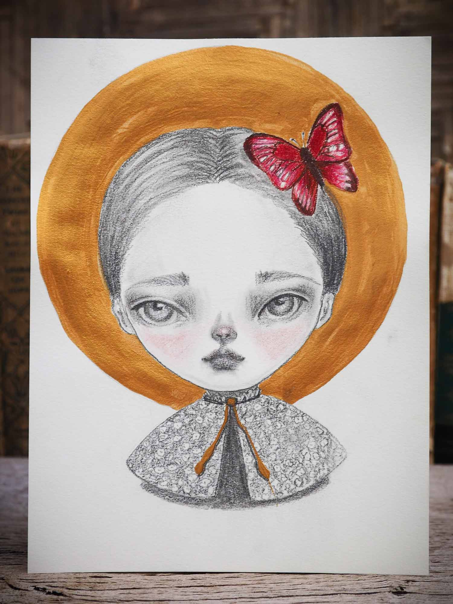 Original mixed media illustration in Pencil, watercolor, gouache and ink by Danita Art. A beautiful girl with deep mesmerizing and expressive eyes has a red butterfly perched on her head like a brooch.