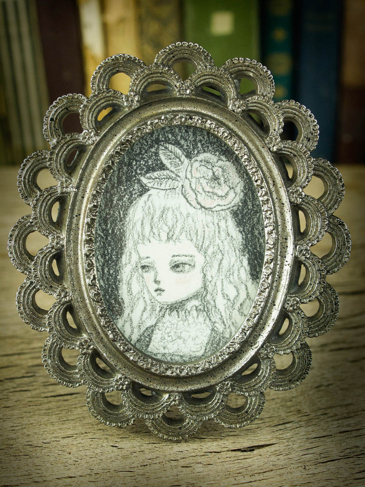 This is a very simple drawing in pencil by Danita Art, with just a little bit of rouge red on her cheeks. I love the vintage style of the image, and the little frame that comes with it it's just perfect for her.