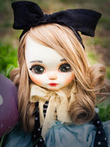 Danita made an Alice in Wonderland handmade art doll, with big expressive gray eyes, super curly blonde hair, a black bow and a blue dress.