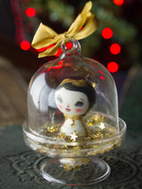 A mini kokeshi wooden art doll handmade by Danita Art, encased in a little glass dome for your Christmas tree.