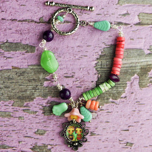 Two sisters enjoy the joy of baking in this original bracelet by Da its Art. Glass beads and jade make this colorful and beautiful piece of wearable art.