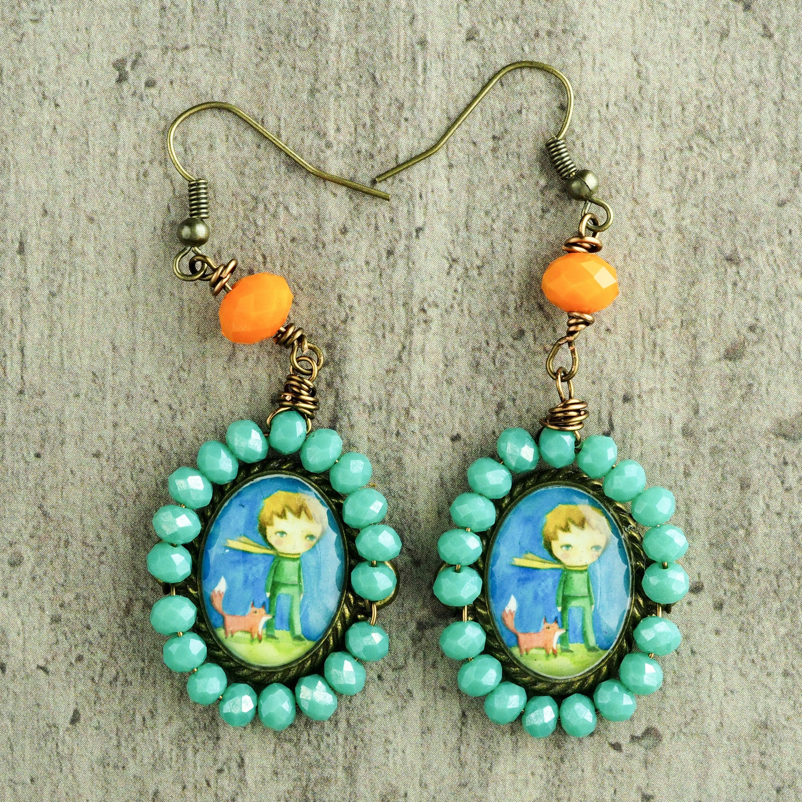 Original one of a kind earrings by Danita. The little prince is painted in the whimsical and surrreal style of Danita. One of a kind original accessories and wearable art.