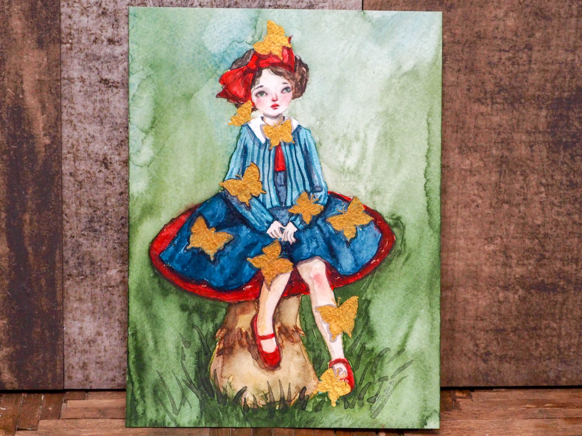 Danita painted herself sitting on a toadstool and surrounded by butterflies in this amazing watercolor original art by Danita. I painted them using a special golden painting I found on trip to Mexico, and they shimmer beautifully with the light!