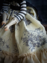 A bunny rabbit girl doll by Danita wears a handmade skirt with vintage patterns.