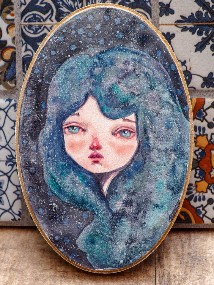 Danita got Inspired by night sky, and she decided to make a few paintings with galaxies and nebulae as inspiration for their hair and faces.   The painting measures 5 x 3 inches on a wood panel, painted using saturated watercolor pigments and my signature melancholic eyes on her face.  Can you can see the beautiful silver dots on her hair? they shine like starts when the light hits them in the right way!