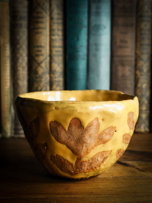 Original fired earthenware ceramic hand pinched bowl with yellow and brown flowers glazed and hand painted motif by Idania Salcido, the artist behind danita Art.