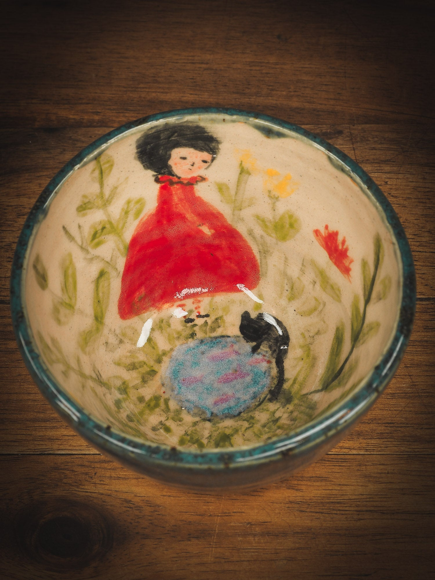 An original Idania Salcido Danita Art pinched ceramic cat pet food plate. Handmade from stoneware, this glazed ceramics one of a kind artwork is perfect for any kitchen plate and bowls unique collection. Thumbprints and  intentionally irregular shape give the bowl a cozy, warmly familiar feel when you pick it. A beautiful cute cat is playing with his girl friend on an underglaze watercolor pond.