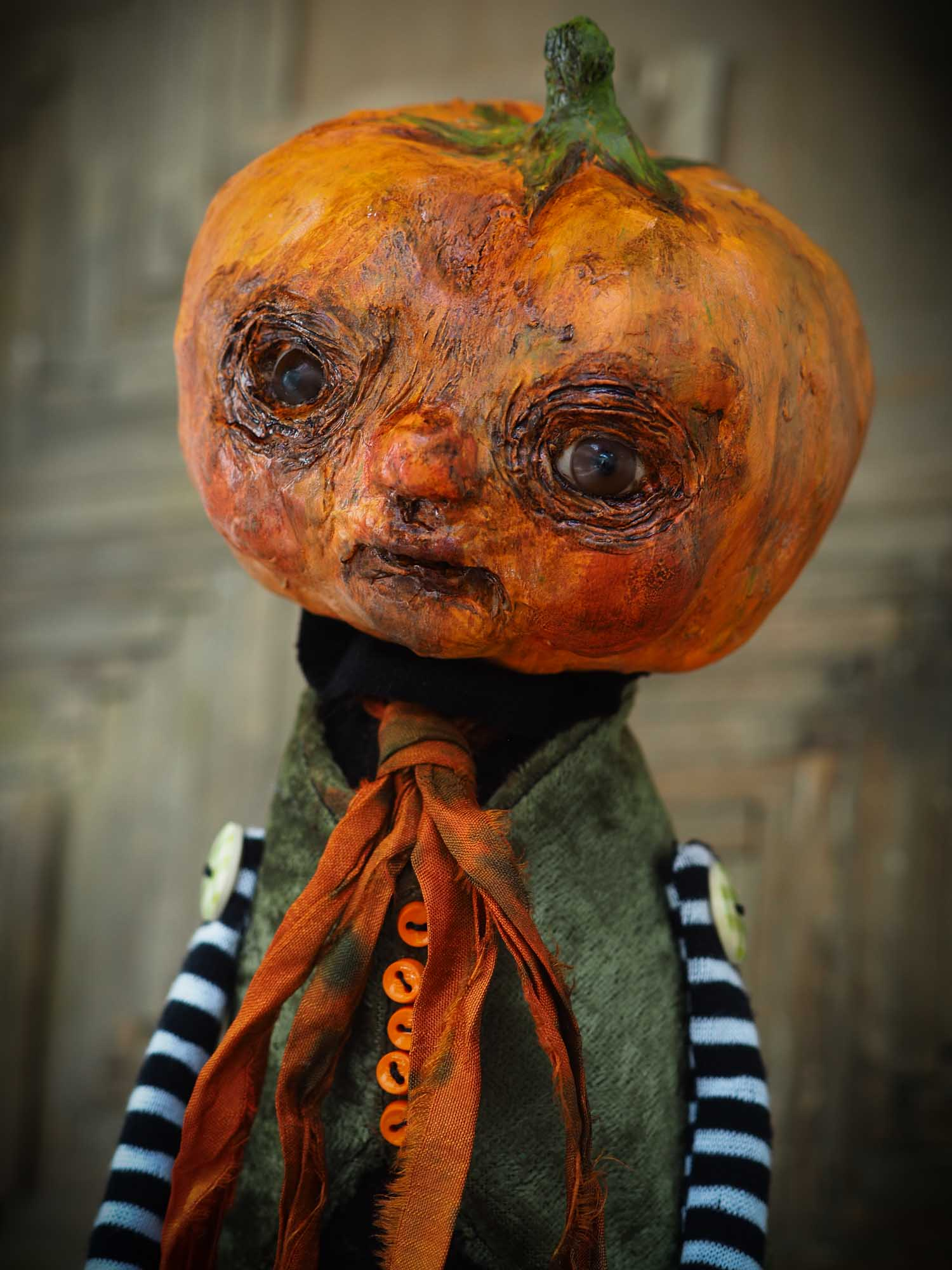 A witch transformed a boy into a Halloween pumpkin monster. This Danita original doll is a handmade jack-o-lantern soft sculpture as home decoration ornament. Carefully handmade with whimsical folk art roots, the spooky ghosts, witches, vampires, ghouls, and jack-o-lantern art dolls of Danita are full of mystery lore.