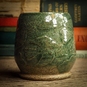 An original glazed ceramic jar by Idania Salcido, the artist behind Danita Art. It measures 2.5 x 2.5 x 3.5 Inches, with deep green hue glazes and hand decorated figures on the sides. Totally handmade in my studio, this is a unique piece that cannot be repeated. Food and drink safe, hand wash only.