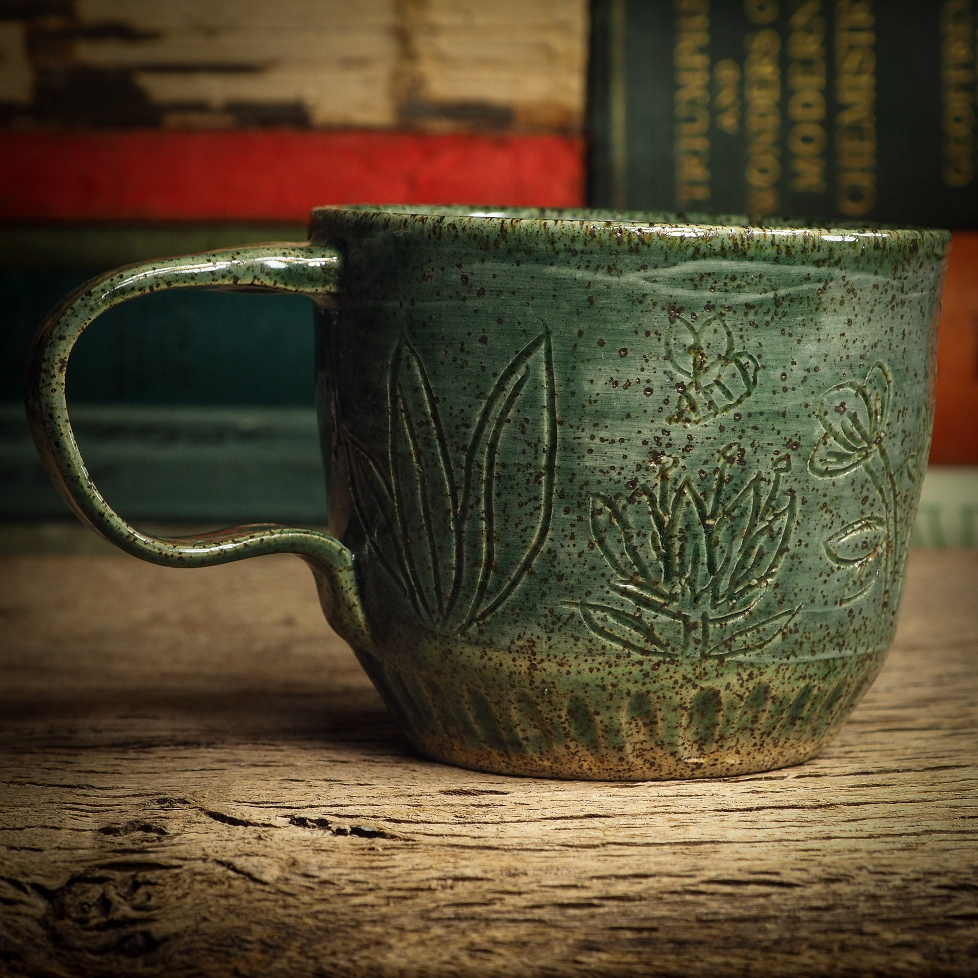 An original glazed ceramic mug by Idania Salcido, the artist behind Danita Art. It measures 3 x 3 x 3 Inches, with deep green hue glazes and hand decorated figures on the sides. Totally handmade in my studio, this is a unique piece that cannot be repeated. Food and drink safe, hand wash only.