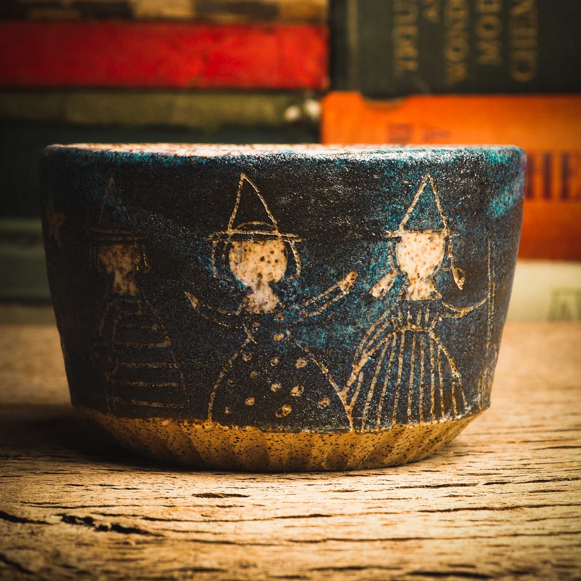 This little handmade ceramic halloween bowl by Idania Salcido Daita art has three witches carved on it, they are ready to cast a spell during a dark starry night, and you can see the magic stream from their wands in subtle bands of color across the deep, midnight blue sky. And of course, the moon and stars are there with them.