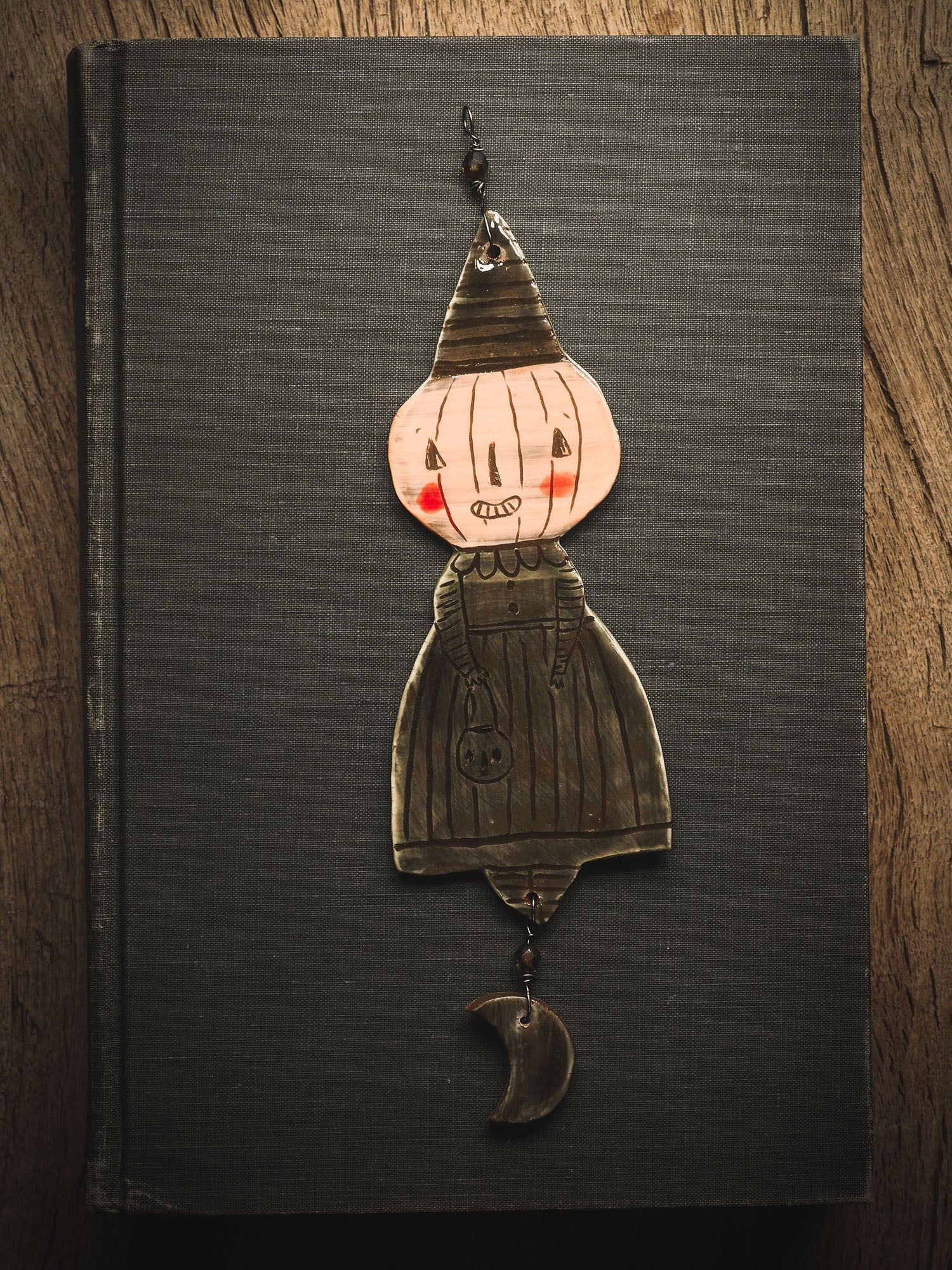 An original handmade Halloween ornament by Idania Salcido, Danita Art. Each ornament is hand carved with pumpkins, witches, cats, jack-o-lanterns and moons.  Made with fired glazed ceramics, this little witch, jack-o-lantern and cat is carved with delicate patterns that make each ornament a one of a kind work of art.