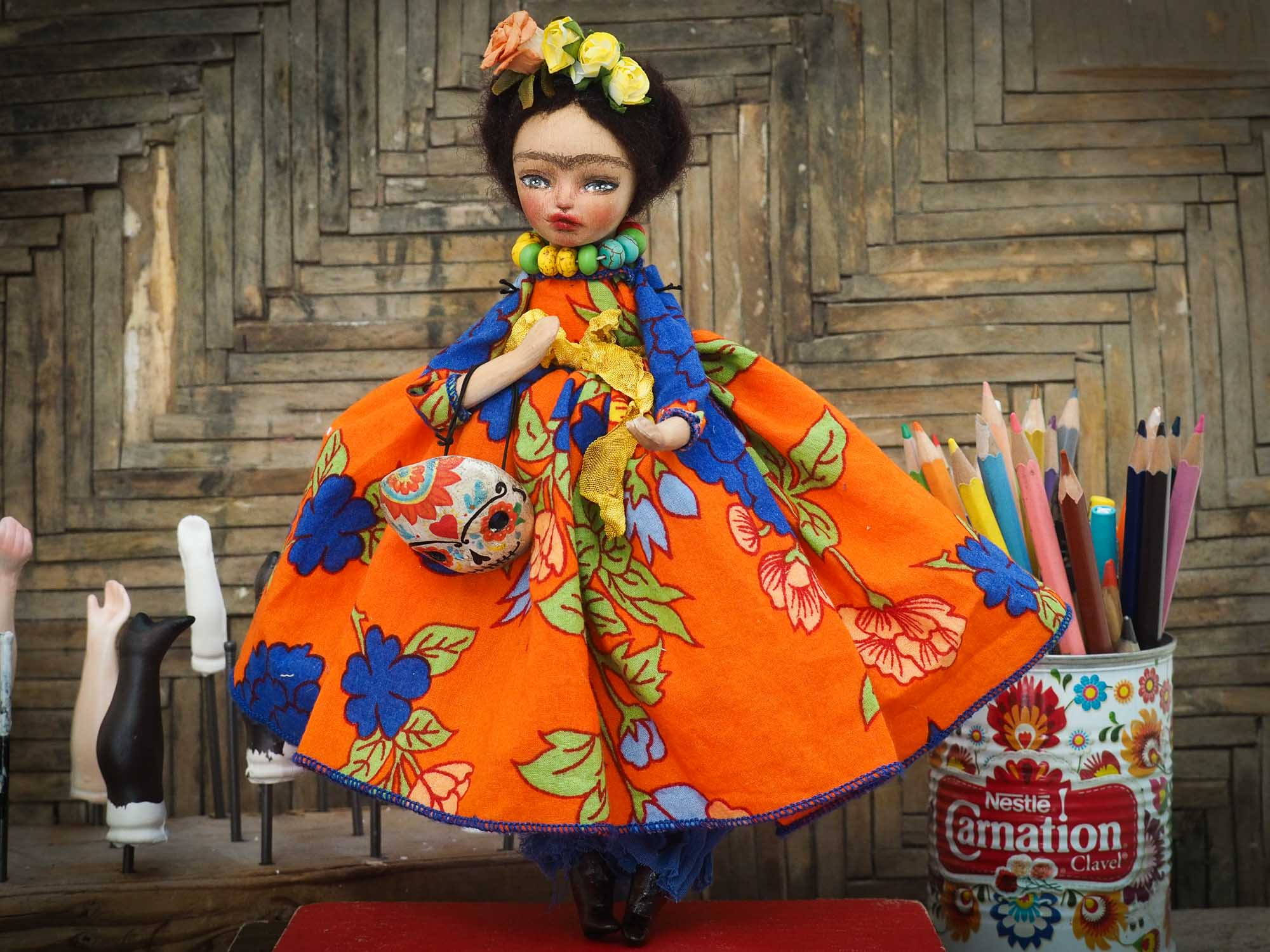 A beautiful handmade art doll by Danita, inspired by Mexican Folk art, Frida Kahlo and The Day Of the Dead. She wears a colorful native motif dress, an unmistakable unibrow, a colorful Dia De los Muertos Catrina skull mask and the signature amazing eyes of Danita Art.