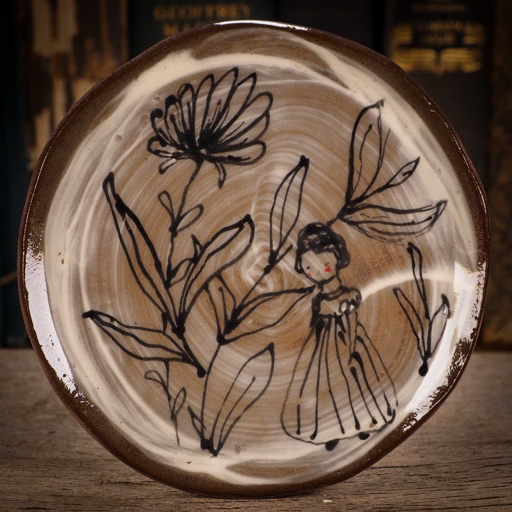 An original glazed ceramic food plate by Idania Salcido, the artist behind Danita Art. Totally handmade in my studio, this is a unique piece that cannot be repeated. Food and drink safe, hand wash only. Brown earth tones and an ink drawing of a girl on the outside.