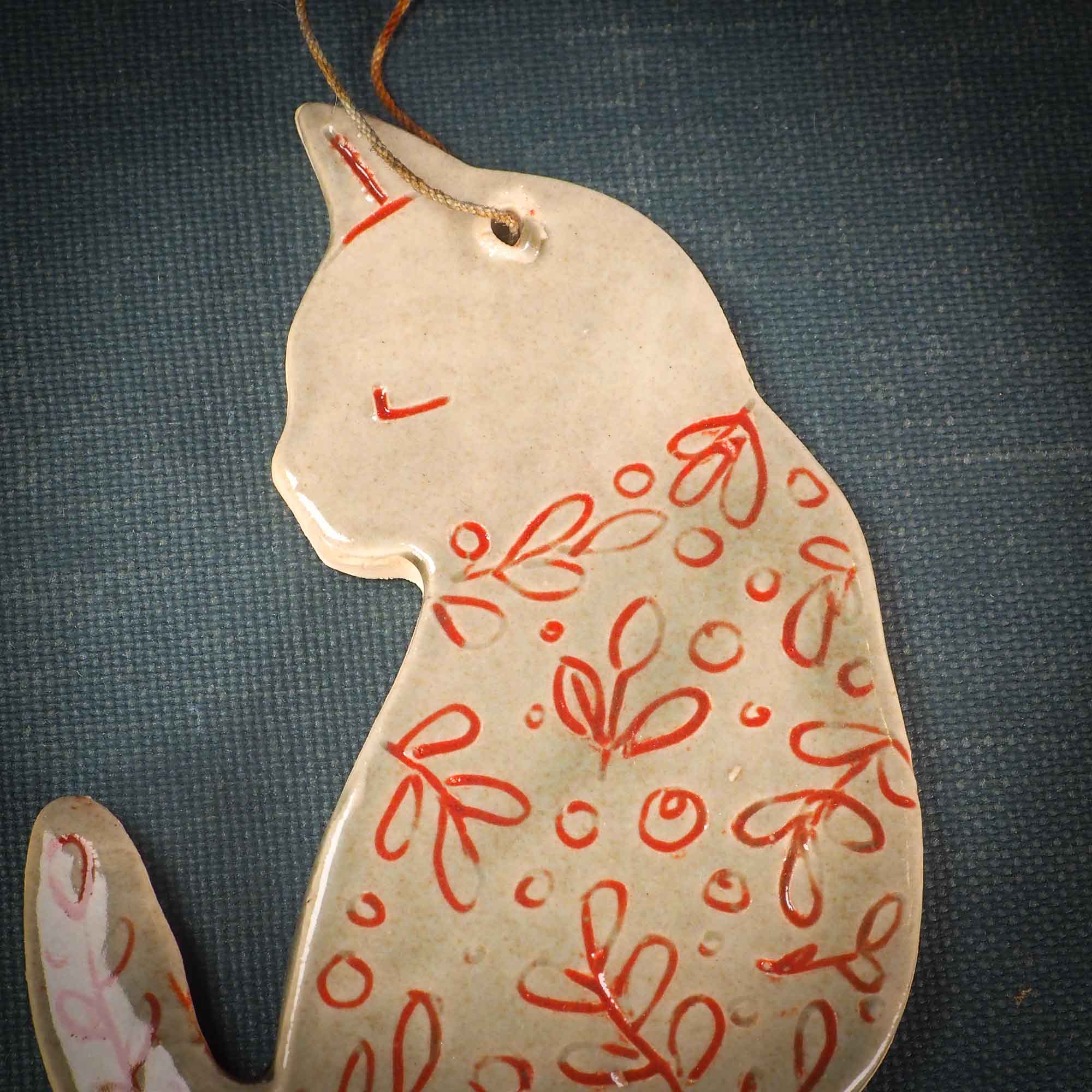 An original Christmas Holiday tree ornament ceramic cat, handmade by Idania Salcido the artist behind Danita Art. Glazed carved sgraffito stoneware, hand painted and decorated, it has a beautiful vintage glass tree ornament to adorn a unique holiday gift for family and friends. Christmas gift for animal and pet lovers.