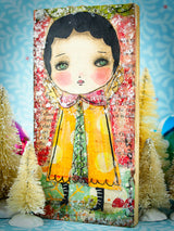 An snowy angel in a yello dress, covered in vintage mica by Danita Art