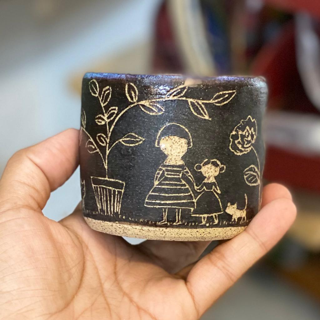 An adorable set of carved ceramic bowl and plate by Idania Salcido, the artist behind Danita Art. The bowl and matching plate are hand made, with carved engravings of the head of woman with flowers inside, and the outside of the bowl has a woman, a girl and a cat in a tree and flower garden.