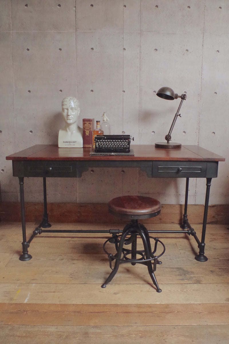 Industrial steampunk Desk with black metal legs and drawers and a wooden top.