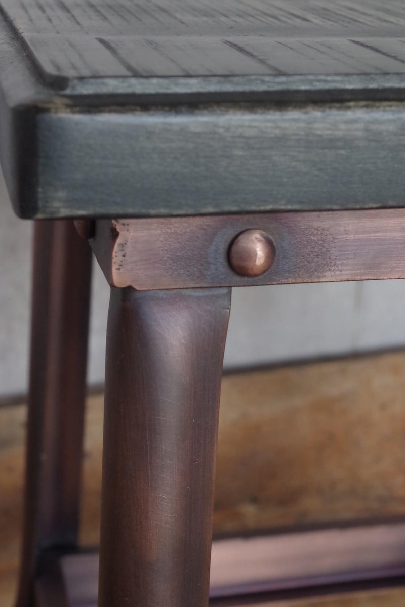 Stool with bronze effect metal legs and black wooden seat.