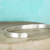 sterling silver inspiration bracelet on teal background