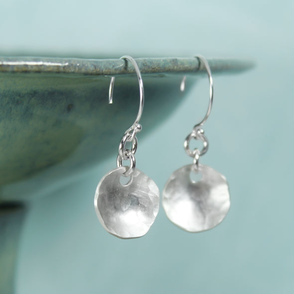 Hammered Silver Drop Earrings on teal Background