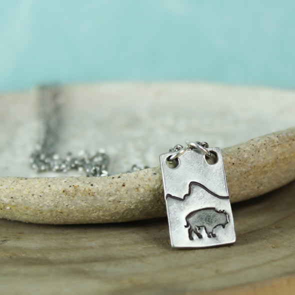 Pewter Bison Necklace on teal and wood background