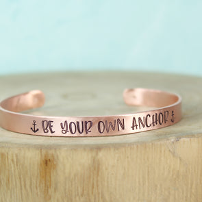Copper Anchor Cuff with teal background on wood