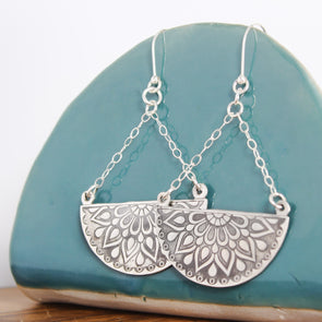 Sterling Silver Mandala Earrings Hanging On Blue Ceramic