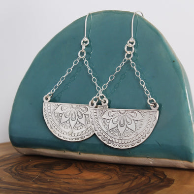 Sterling Silver Mandala Earrings hanging on teal ceramic