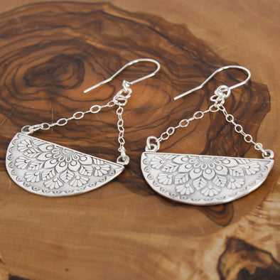 Silver Floral Mandala Earrings on wood background