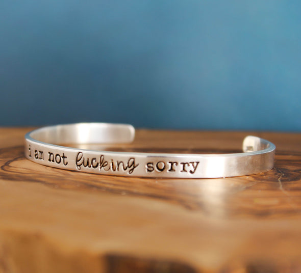 not sorry inspiration cuff bracelet on wood background