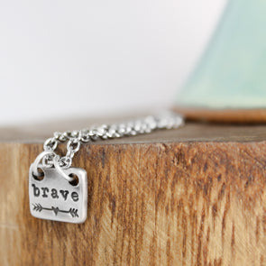hand stamped brave necklace on wood block