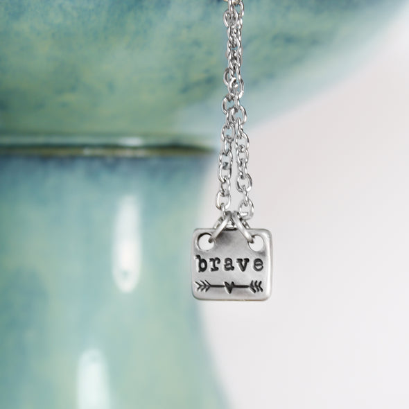hand stamped brave necklace with white and teal background
