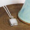 Selenite Ornate Rectangle Necklace on wood block