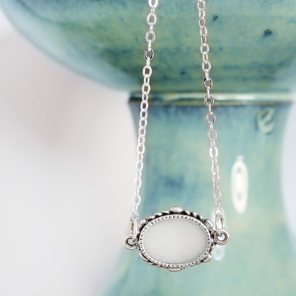 Oval Selenite Necklace on White & Teal Background