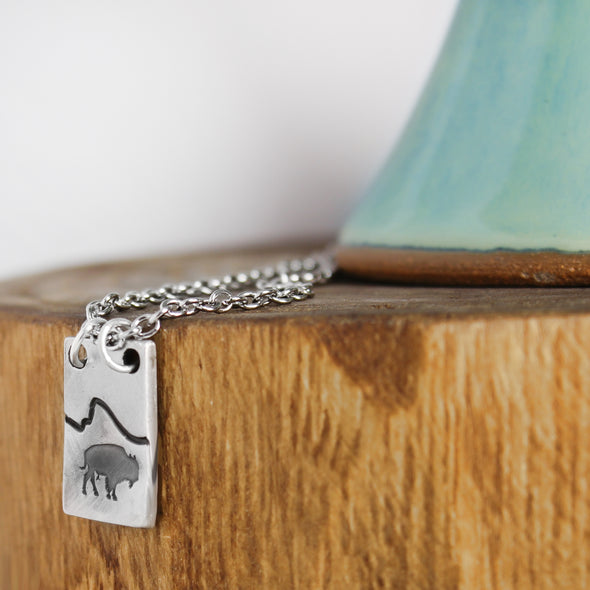 Pewter Bison Necklace on wood and white background