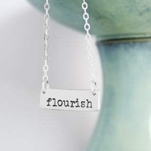 Sterling Silver Flourish Necklace on White and Teal Background