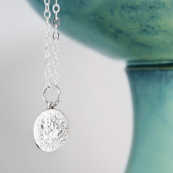 Silver Textured Moon Necklace on White Background with teal accents