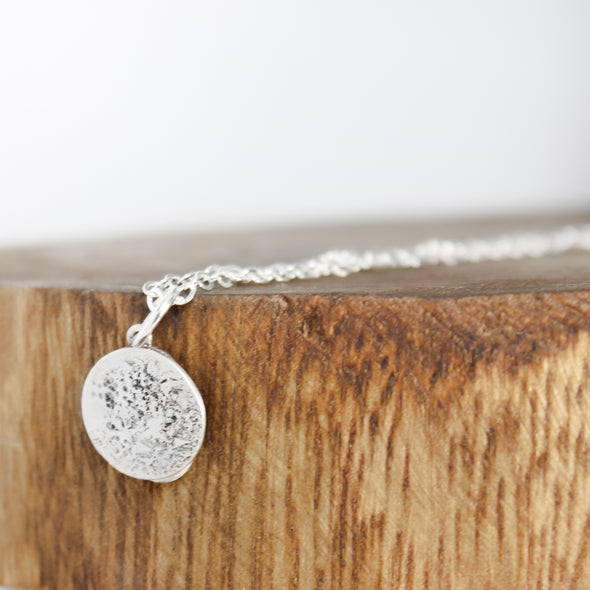 Silver Textured Moon Necklace on wood block