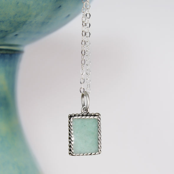 turquoise pendant on white and teal background