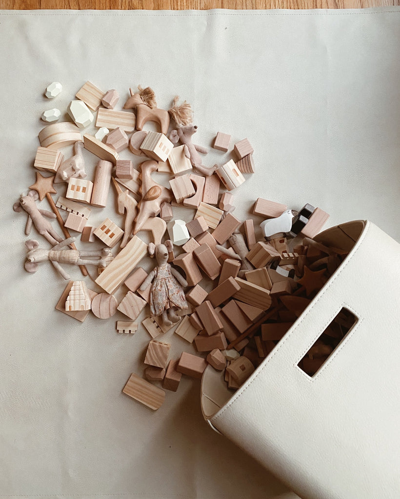 White Storage Bin with wooden toys spilling out
