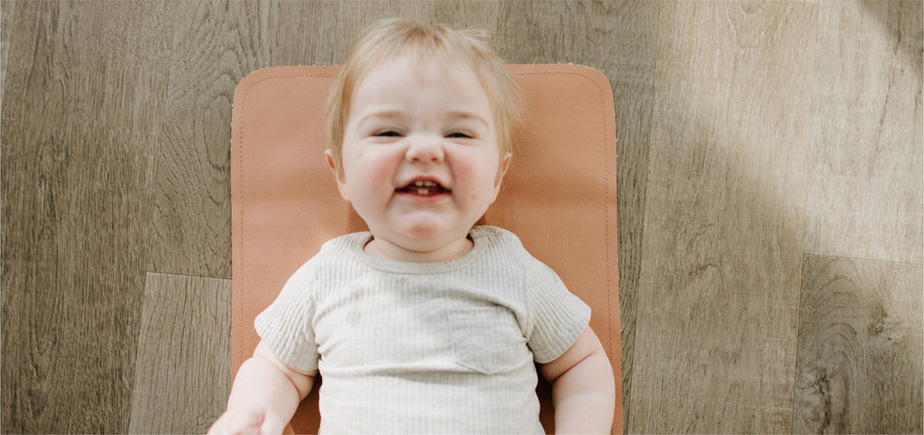 smiling baby on leather changing mat
