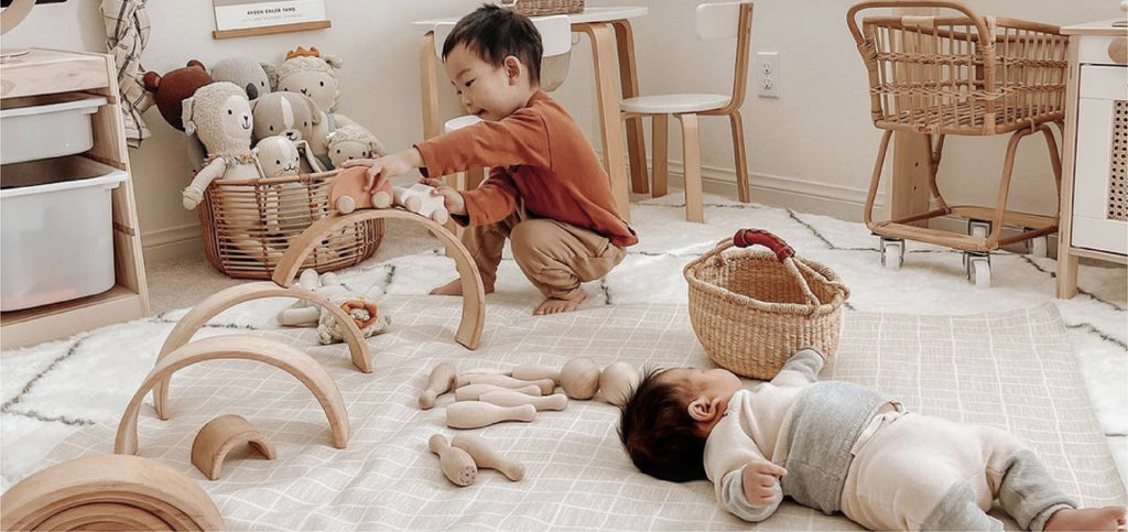 children playing on leather mat with wood toys